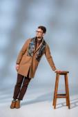 volle Länge der stilvolle Mann im Winter-Outfit und Brille lehnt auf Holzstuhl in der Nähe Aktentasche auf grau