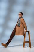Fotografie in voller Länge trendiger Mann in Wintermantel und Brille, angelehnt an Holzstuhl auf grau