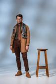 Fotografie Stilvoller Mann in winterlichem Outfit und Brille, der neben einem Holzhocker auf grau steht