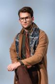 Fotografie stylischer Mann im Winteroutfit und Brille auf Stuhl sitzend auf grau