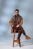 stylischer Mann im Winteroutfit und Brille sitzt mit der Hand in der Tasche auf Holzstuhl neben Aktentasche auf grau