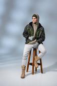 in voller Länge junger trendiger Mann mit Hut und Anorak sitzt auf einem Holzhocker auf grau