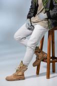 Ausgeschnittene Ansicht eines jungen trendigen Mannes mit Hut und Anorak, der auf einem Holzhocker in Grau sitzt