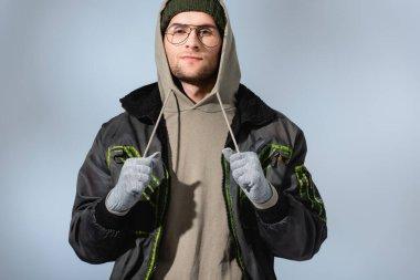 Gözlüklü, şapkalı, anorak ve eldivenli şık bir adam grideki kameraya bakıyor.
