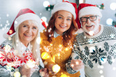 joyful senior couple with daughter in santa hats holding sparklers while looking at camera, bokeh lights illustration