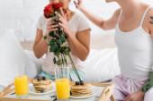 abgeschnittene Ansicht einer lesbischen Frau, die rote Rosen in der Nähe von Freundin und Frühstück im Bett riecht