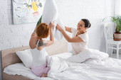 cheerful interracial lesbians having fun with pillow in bedroom