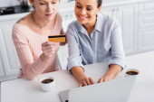 cheerful african american woman typing on laptop near lesbian girlfriend holding credit card