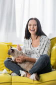 excited woman laughing while sitting on yellow sofa with cat