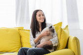 cheerful woman looking away while embracing cat on sofa