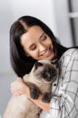 happy young woman smiling while hugging cat at home