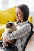 usmívající se žena se sluchátky na krku objímající kočku doma