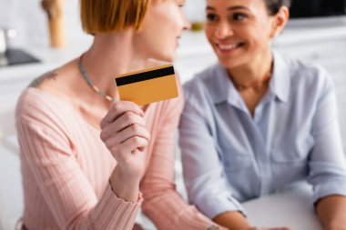 Selective focus of credit card in hand of lesbian woman looking at cheerful african american girlfriend, blurred background stock vector