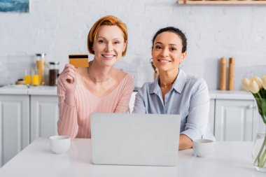 Happy redhead woman with credit card and her cheerful african american girlfriend looking at camera near laptop stock vector
