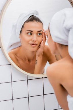Young woman with white terry towel on head tweezing eyebrows in bathroom near mirror, blurred foreground stock vector
