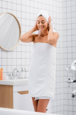 Happy young woman with closed eyes fixing white terry towel on head in bathroom stock vector