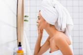 Seitenansicht einer Frau mit weißem Handtuch auf dem Kopf beim Zähneputzen im Badezimmer, verschwommener Vordergrund