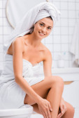 cheerful woman with white towel on head smiling at camera while applying body lotion on leg in bathroom
