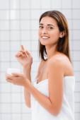 boldog fiatal nő arckrém az orrán nézi kamera a fürdőszobában