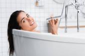 boldog fiatal nő nézi a kamera, miközben fürdik, és beszél a mobiltelefon