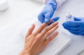částečný pohled na manikúra držícího odstraňovač kůžičky při dotyku prstu klienta