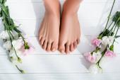 vrchní pohled na ženské nohy s pastelově růžovými nehty u karafiátů a eustomových květin na bílém dřevěném povrchu