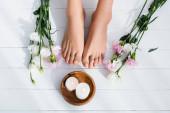 pohled shora na upravenou ženskou nohu, mísu se svíčkami, eustomu a karafiáty na bílém dřevěném povrchu