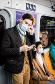man in medical mask and headphones using smartphone near african american woman in subway
