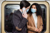african american woman in medical mask looking at boyfriend talking on smartphone in subway