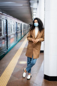 Photo full length of curly african american woman in medical mask standing in subway