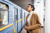 kudrnaté africké americké ženy při pohledu na vůz metra na rozmazaném pozadí