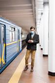 plná délka člověka v lékařské masce drží smartphone v blízkosti vozu metra