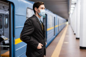 man in medical mask standing with hands in pockets near wagon of metro