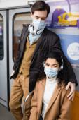man in headphones hugging african american woman in medical mask in subway
