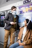 muž ve sluchátkách drží smartphone a při pohledu na africké Američanky v lékařské masce v metru