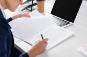 Ausgeschnittene Ansicht eines Teamleiters mittleren Alters bei Vertragsunterzeichnung auf dem Schreibtisch