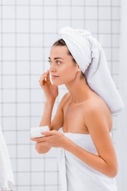 Young woman with towel on head applying face cream in bathroom stock vector