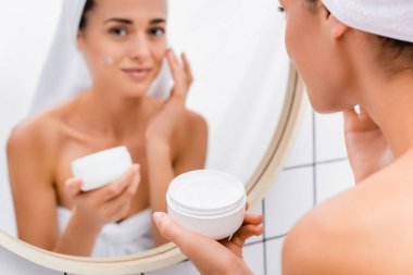 Young woman applying face cream near blurred mirror reflection in bathroom stock vector