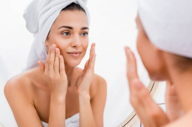 Young woman with towel on head applying facial scrub while looking in mirror, blurred foreground stock vector