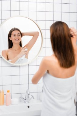 Smiling woman, wrapped in white towel, using deodorant near mirror in bathroom, blurred foreground stock vector