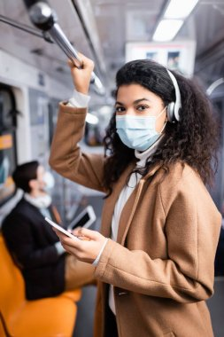 curly african american woman in medical mask listening music and using smartphone in subway