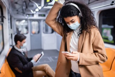 Young african american woman in medical mask listening music and using smartphone near man in subway on blurred background stock vector