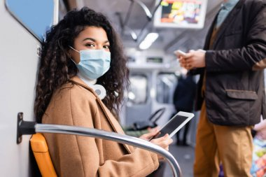 young african american woman in medical mask using digital tablet near man in subway with blurred background