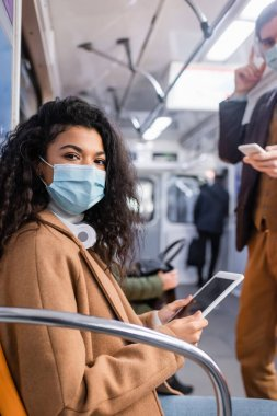 african american woman in medical mask using digital tablet near man in subway with blurred background