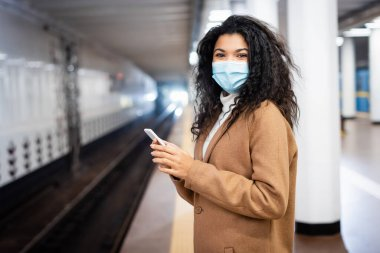 curly african american woman in medical mask using smartphone in subway