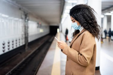 curly african american woman in medical mask using cellphone in subway