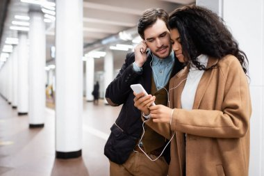 multicultural couple looking at smartphone while listening music in earphones in subway