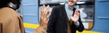 Partial view of happy interracial couple waving hands near wagon in metro, banner stock vector