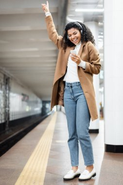 full length of excited african american woman in wireless headphones using smartphone while listening music in subway