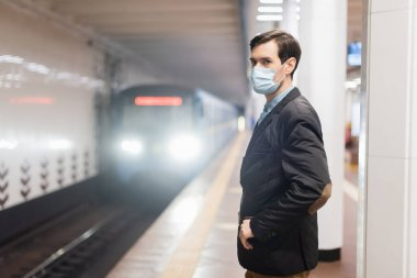 man in medical mask standing with hand in pocket near wagon of metro
